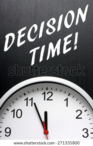 The phrase Decision Time in white text on a blackboard above a modern clock face with the time at almost midnight or twelve noon