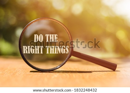 The phrase Do The Right Things typed on a magnifier glass. A reminder to make the right choices according to your moral compass. Сток-фото ©