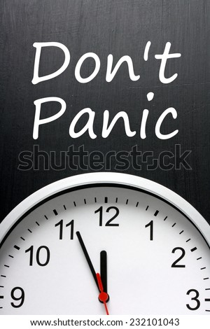 The phrase Don\'t Panic written on a blackboard above a clock with the time set at five minutes to or almost midnight or high noon