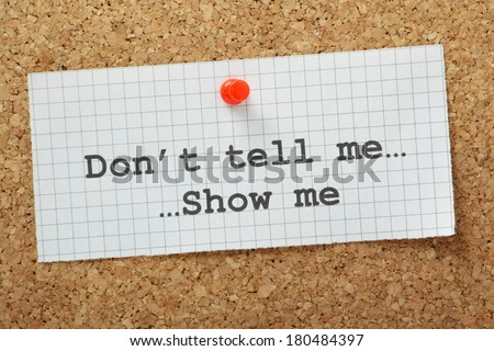 The phrase Don't Tell Me Show Me typed on a piece of graph paper and pinned to a cork notice board Often used in business but more so as a guide for novel and book writers