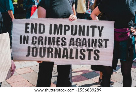 "The phrase "" End impunity in crimes against journalists "" drawn on a carton banner. A girl holds a cardboard with an inscription. Girls on the street. Protest. News Media. Crime. Freedom"