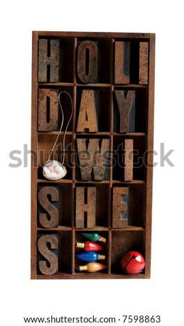 the phrase 'holiday wishes' in a type case with vintage Christmas light bulbs, a red jingle bell and a baby Jesus in a walnut shell