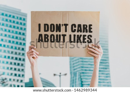 """The phrase """" I don't care about likes """" drawn on a carton banner in men's hand. Human holds a cardboard with an inscription: I don't care about likes #1462989344"""