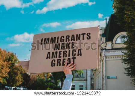The phrase ' Immigrants Make America Great ' on a carton banner in men's hand. Human holds a cardboard with an inscription. Immigration. Protest Сток-фото ©