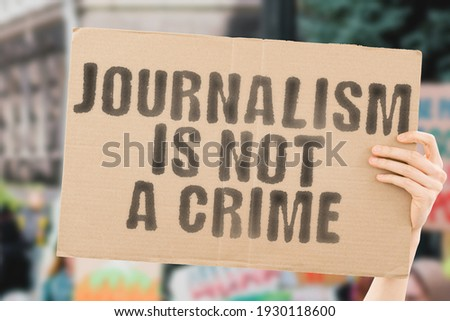 The phrase ' Journalism is not a crime ' on a banner in hand with blurred background. Protest. Street. Strike. Punishment. Power. Pressure. Offence. Criminality. Dishonesty. Free. Freedom of speech Photo stock ©