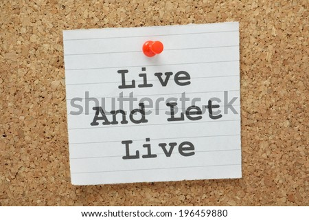 The phrase Live and Let Live typed on a paper note and pinned to a cork notice board