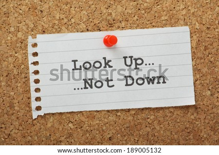 The phrase Look Up, Not Down typed on a paper note and pinned to a cork notice board.
