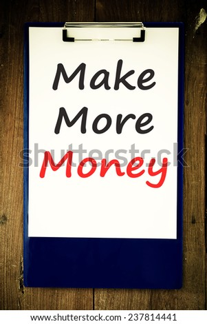 The phrase Make More Money typed on a piece of note paper and pinned to a cork notice board