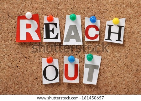 The phrase Reach Out in cut out magazine letters pinned to a cork notice board. We reach out to colleagues at work for assistance and to organizations and communities for help and support.