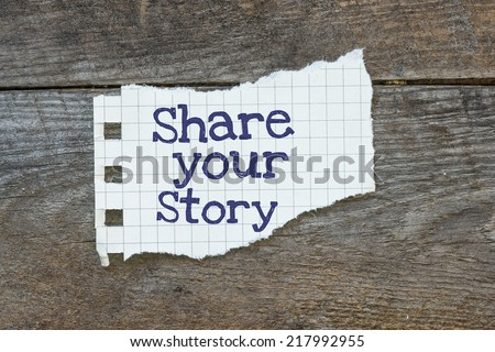The phrase share Your Story typed on a piece of lined paper on wooden board