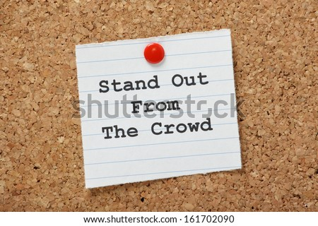 The phrase Stand Out From The Crowd on a paper note pinned to a cork notice board. It is important to demonstrate the differences or unique skills we can bring to a new job or relationship.