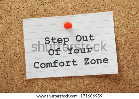 The phrase Step Out of Your Comfort Zone on a paper note pinned to a cork notice board. A concept for moving beyond your current circumstances to embrace new opportunities.