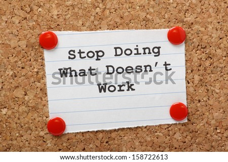 The phrase Stop Doing What Doesn't Work on a paper note pinned to a cork notice board. In both business and our own lives we have to look for efficiency and best practice to move forward. Stock photo ©