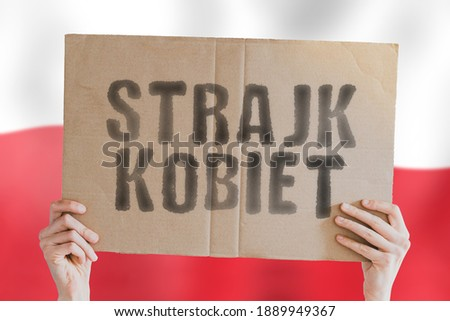 The phrase ' Strajk Kobiet ' on a banner in men's hand with blurred Polish flag on the background. Government. Control. Illegal. Freedom. Human rights. Protest. Movement Zdjęcia stock ©