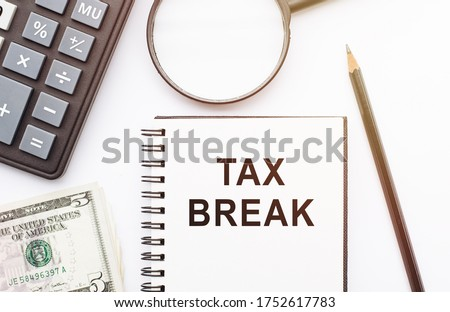 The phrase Tax Break in notebook with calculator, magnifier, money and pen background on white table. Business and financial concept Stock photo ©