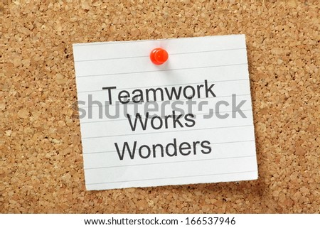 The phrase Teamwork Works Wonders typed on a piece of lined paper and pinned to a cork notice board