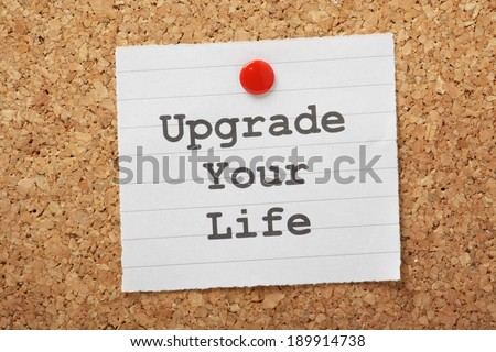 The phrase Upgrade Your Life typed on a piece of paper and pinned to a cork notice board
