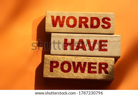 The phrase Words Have Power on wooden blocks laying on orange background. Copywriting advertising PR concept. Stockfoto ©