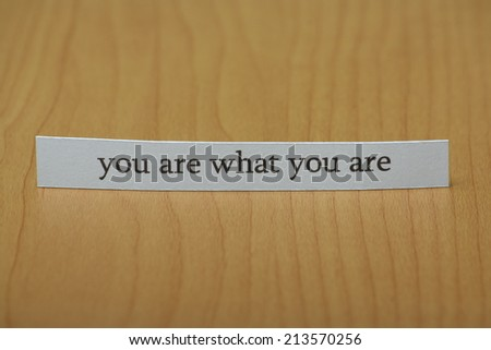 The phrase you are what you are typed on a strip of white paper and left standing on a wooden desktop surface