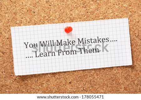 The phrase You Will Make Mistakes, Learn From Them typed on a piece of graph paper and pinned to a cork notice board. A way of empowering people on their road to success.