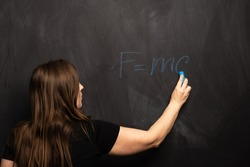 The physical formula of Einstein's theory is written by a young girl in blue chalk on a blackboard. FMC2 is written by a science teacher or student in the classroom.
