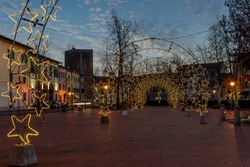 The Piazza Vittorio Emanuele II in the center of Bientina, Pisa, Tuscany, Italy, fully decked out with Christmas lights for the seasonal holidays, at sunset