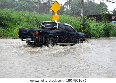 The pickup truck is passing the urban road which fulled of the floodwater on the heavy raining day because of the Hegos storm. (Defocused) Stock fotó ©