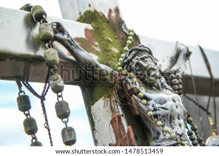 The picture from the hill of crosses by Šiauliai in Lithuania. Many crosses on this religious places and many of them old and abandoned. Detail of one Jesus.