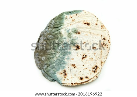 The picture of a mouldy flatbread. Rotten and uneatable. Isolated on white background.  Stock photo ©