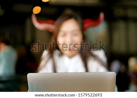 The picture of a woman with devil horn making Cyberbullying and fake business news in an office. #1579522693