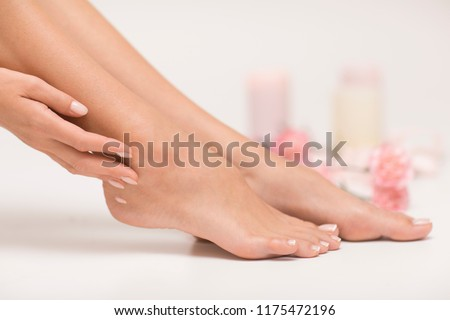 The picture of ideal done manicure and pedicure. Female hands and legs in the spa spot. #1175472196