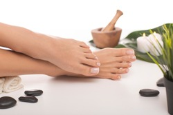 The picture of ideal done manicure and pedicure. Female hands and legs in the spa spot in the white background.