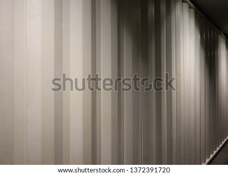 The picture of light beige container wall. Brightening by light bulb from the top. Backgrounf container wall picture. Copy space for editing #1372391720