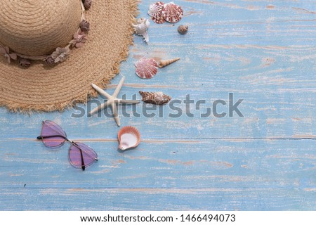 The picture placement the sea concept. Holiday travel. There are hat for women Shells Starfish and sunglass. Blue wooden background.