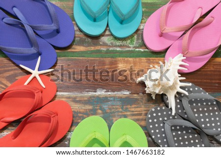 The picture placement the sea concept. Holiday travel. There are many multicolor sandals shells and starfish. Background is a wooden board green brown color.