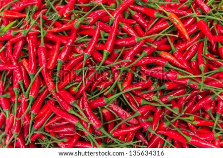 The Picture Shows A Pile Of Small, Red, Very Hot And Spicy Chilli Peppers On An Asian Market.