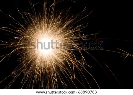 The picture shows a sparkler on black background .