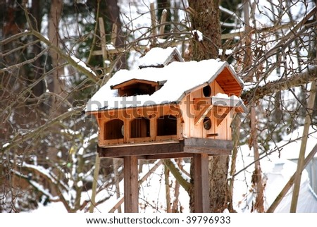 the picture shows a very luxurious birdhouse with snow on it