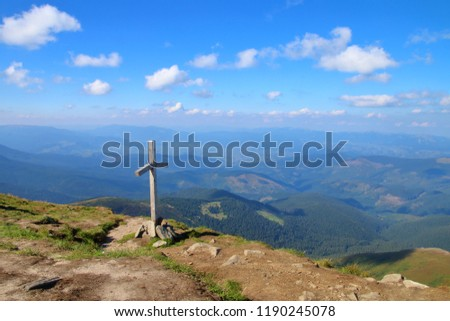 The picture was taken in Ukraine, on top of a mountain called Goverla. In the photo there is a wooden cross against the sky and clouds. #1190245078