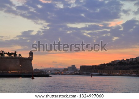 The picture was taken on the island of Malta, from the pier of the city of Birgu. In the photograph the Tower is called Vedette on the fortress wall of the former fort, in the rays of the setting sun. Stock fotó ©