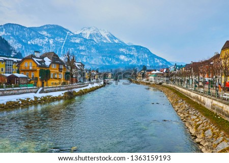 The picturesque Alpine scenery with snowy Mount Katrin from the Traun river, lined with histroical edifices of Bad Ischl, Salzkammergut, Austria.
