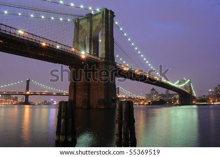 The Picturesque Brooklyn Bridge shimmering at night as it spans the east river in New York City. #55369519