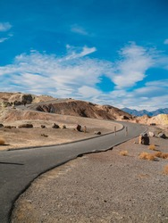 The picturesque empty road in Death Valley with a view of the hills