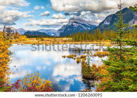 The picturesque lake Vermilion. Warm sunny autumn day. Lush cumulus clouds are reflected in the smooth water of the lake. The concept of ecological, photographic and active tourism #1206260095