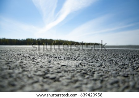 The picturesque landscape and the Sunrise over the road. Asphalt road with marking. With the blur. #639420958