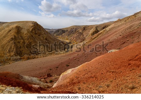 The picturesque steppe desert landscape with multicolored mountains, cracks in the ground and sparse vegetation on the background of other mountains and cloudy sky in autumn