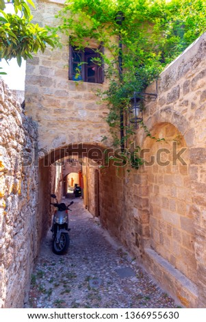 The picturesque streets of Rhodes medieval Old Town, Rhodes, Greece. Very narrow street in City of Rhodes, Dodecanese, Greece, in a sunny day. Ancient stone walls covered in lush green jasmine