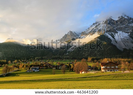 The picturesque village in the foothills of the Alpine peaks on a spring day, beautifully colored meadows in evening sun, Austria, Dachstein