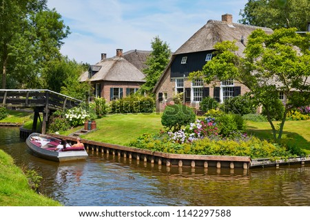 The picturesque village of 'Giethoorn' in the province of 'Overijssel', also called 'Venice of the North' because of the many water canals where tourists do their sightseeing from a boat #1142297588