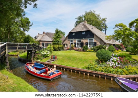 The picturesque village of 'Giethoorn' in the province of 'Overijssel', also called 'Venice of the North' because of the many water canals where tourists do their sightseeing from a boat #1142297591